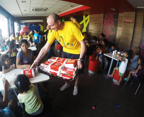 Mike handing out breakfast meals to the kids.