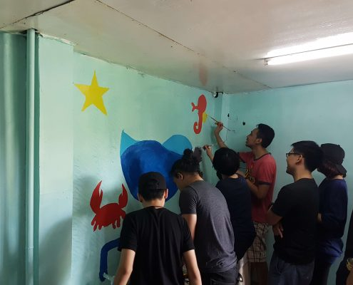 Rommel painting a seahorse for the mural